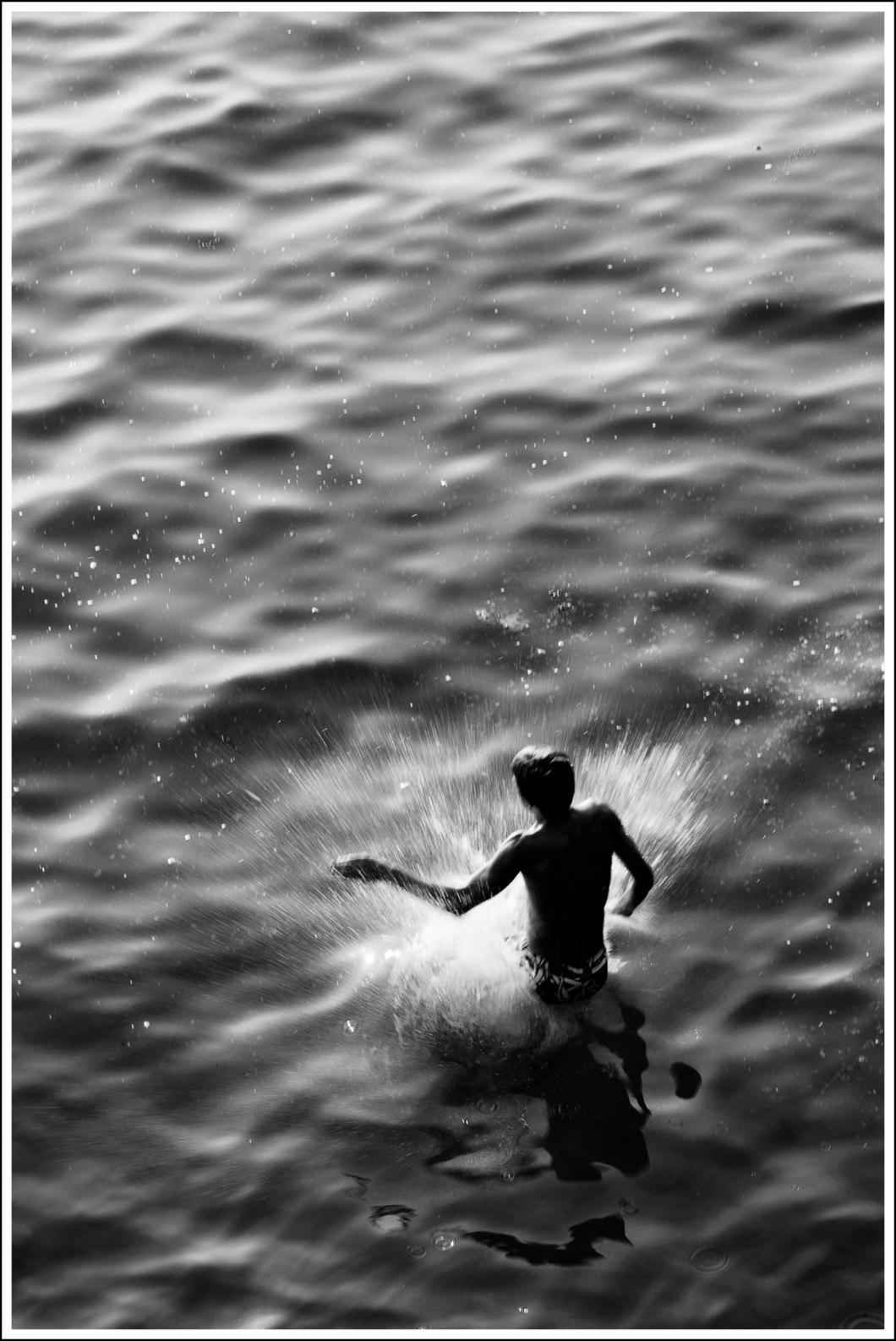 Un niño saltando desde unas rocas.